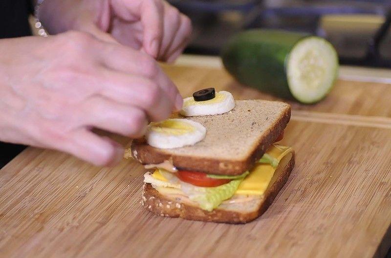 Para decorar el sándwich y darle la figura de búho colocar dos rebanadas de huevo cocido y encima una rebanada de aceituna negra para formar los ojos.