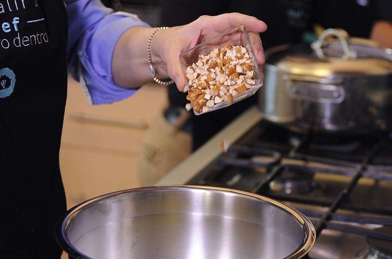Añadir perejil picado, almendras picadas, y el ajo picado en un tazón. Revolver bien con la pala.