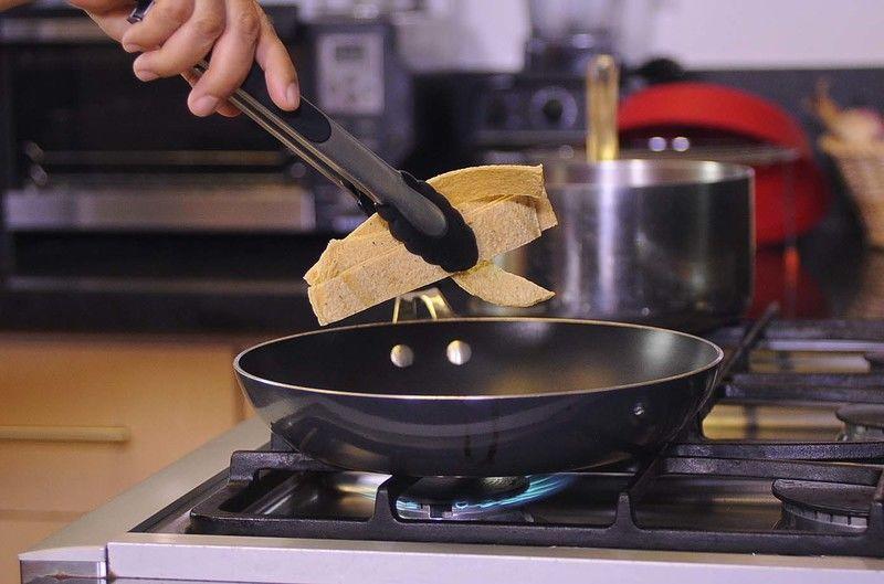 Calentar el aceite de oliva en una sartén y freír las tortillas cortadas en tiras, moviéndolas constantemente hasta que queden doradas pero no quemadas.