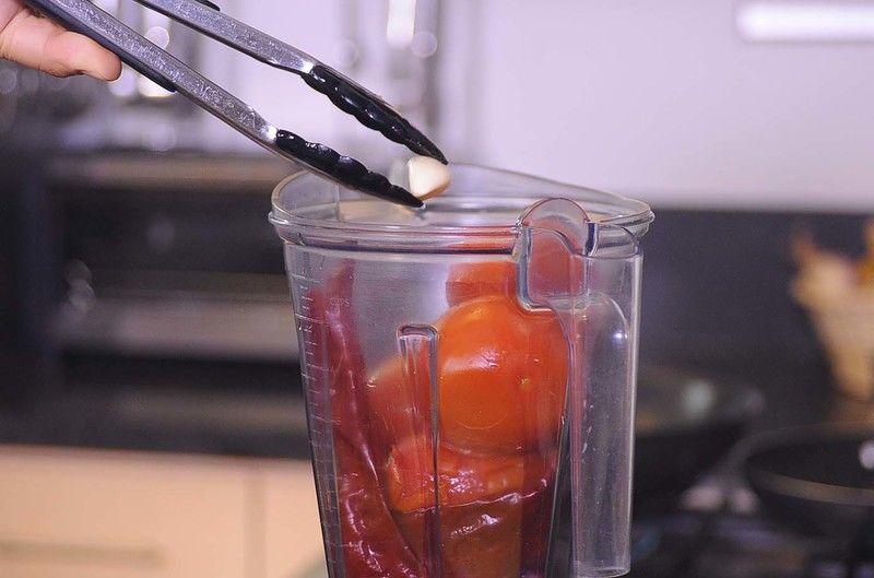 Colocar los chiles guajillo hervidos, jitomates y el ajo en el vaso de la licuadora y moler hasta obtener una mezcla homogénea.
