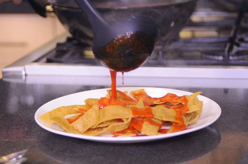 Colocar en un plato las tortillas fritas. Bañar muy bien con la salsa
