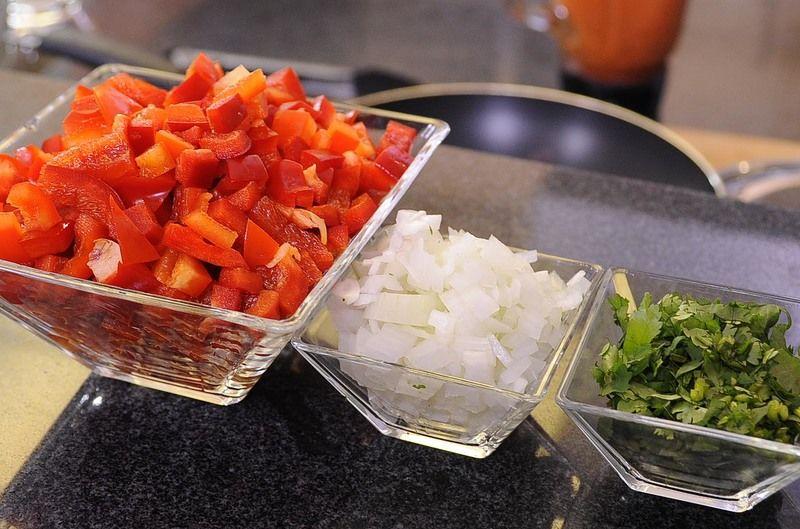 Picar finamente la cebolla y cilantro, cortar los pimientos en cubos pequeños descartando la parte blanca. Reservar