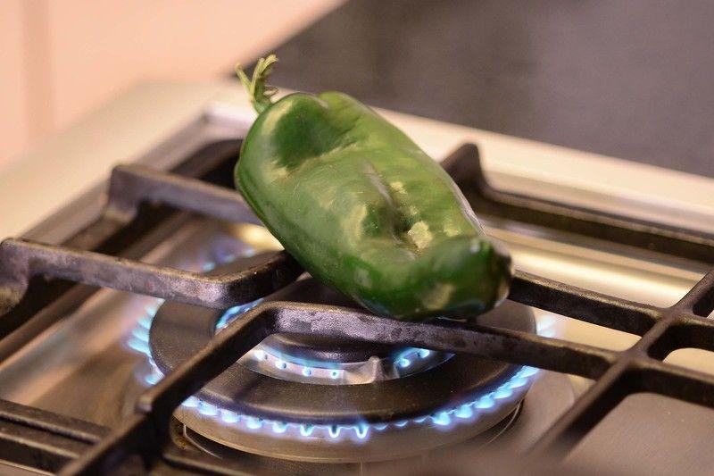 Para preparar la salsa; asar los chiles poblanos directamente sobre la hornilla de la estufa, dándoles vuelta con una pinza hasta que la piel esté tostada por todos lados.