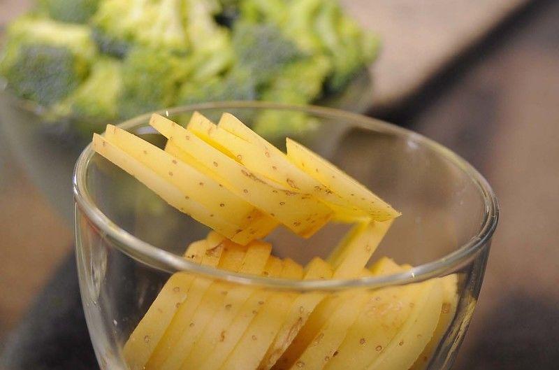 Picar finamente el diente de ajo y las hojas de albahaca. Cortar las papas en rebanadas delgadas.