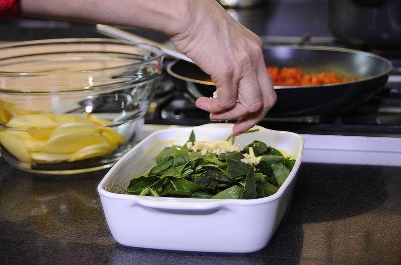 Agregar la salsa de jitomate, hojas de espinaca y el queso manchego rallado.