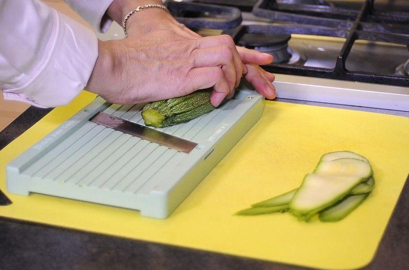 Colocar la mandolina en una tabla de picar y cortar las calabacitas en láminas delgadas, reservar.