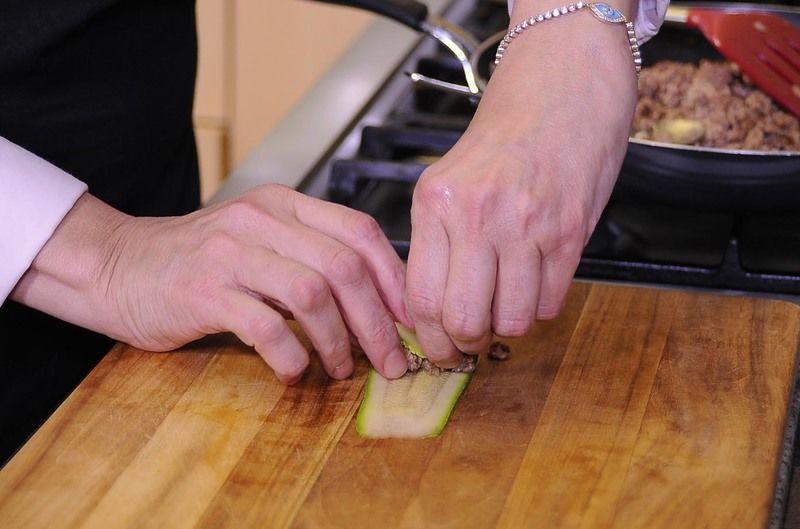 Colocar sobre la tabla de picar una lámina delgada de calabacita y rellenar con un poco de la mezcla de carne y enrollar.
