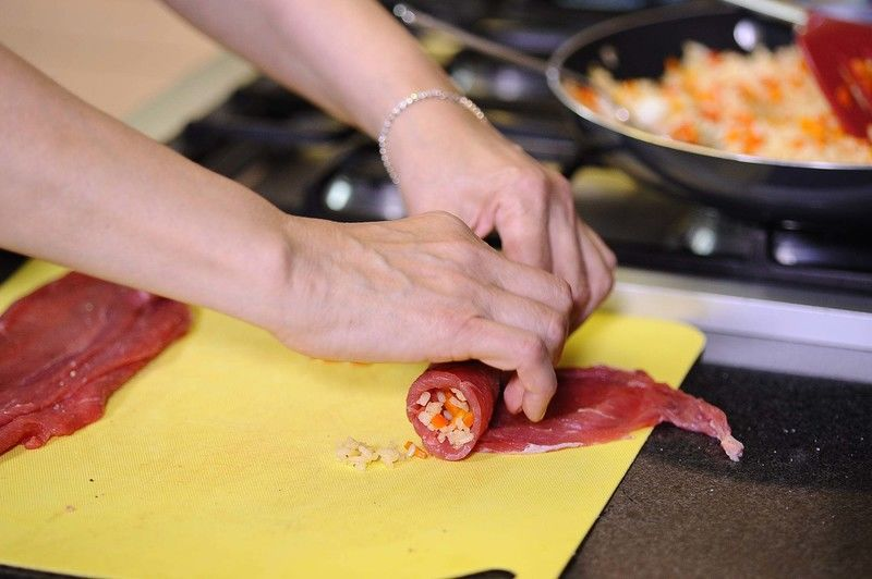 Añadir un poco de arroz y enrollar, asegurar con palillos para que no se habrán los rollos.