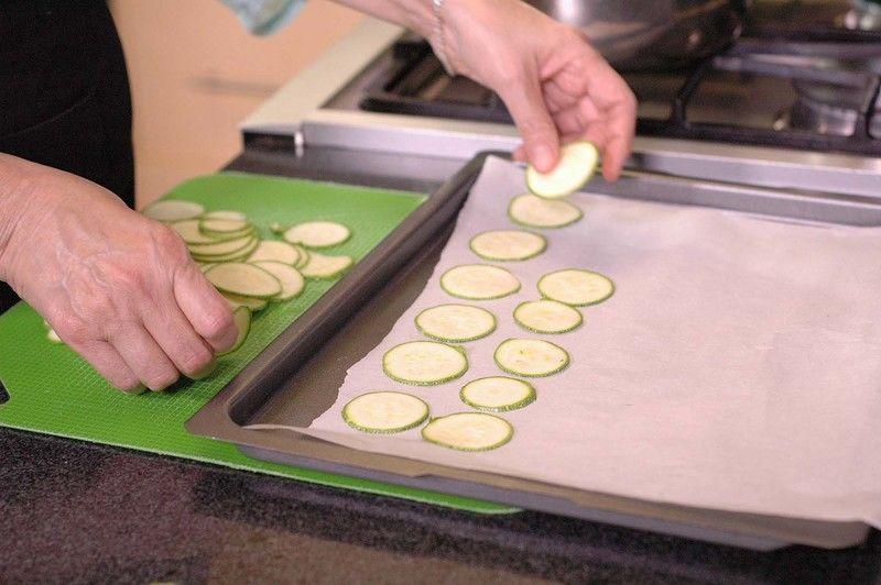 Colocar el papel encerado sobre la charola para horno y poner las rebanadas de calabacita sobre e papel, dejando un espacio entre cada rebanada.