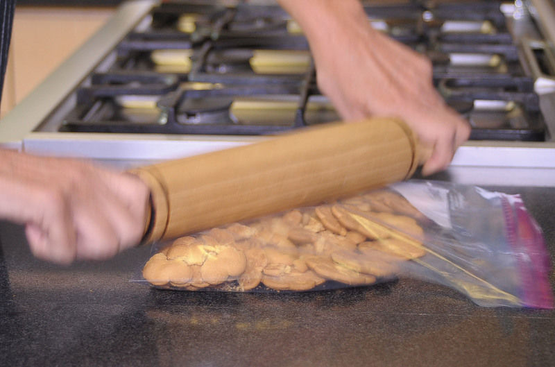 Precalentar el horno a 350º F Meter las galletas en una bolsa de plástico y moler con un palote. Poner en el molde y agregar la mantequilla derretida, aplastar sobre el molde y meter al horno de 10 a 15 minutos. En un tazón batir la crema hasta formar picos suaves, agregar el azúcar y la esencia de vainilla. Agregar el dulce de leche sobre las galletas y acomodar el plátano rebanado agregar la crema batida, adornar con chocolate rallado y meter al refrigerador hasta la hora de servir.