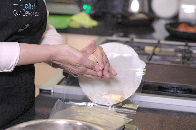 Tomar una bola de masa con la mano y formar una bolita. Hacer u hueco en la bolita de masa y añadir un poco de chicharrón prensado.