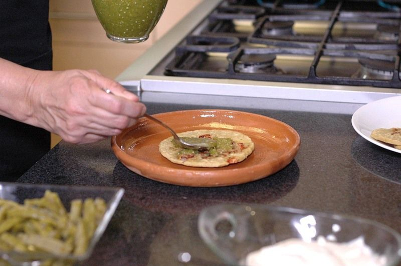 Para servir colocar una gordita en el plato, añadir un poco de salsa verde sobre ella.