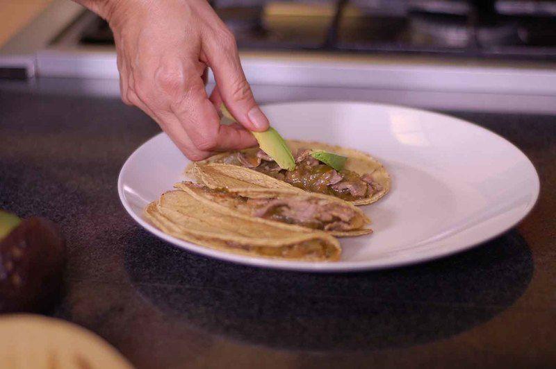 Para servir calentar las tortillas en el comal o sartén y rellenar con un poco del guisado y rebanadas de aguacate.