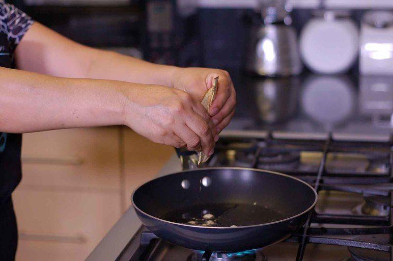 Calentar el aceite en el sartén y cuando esté caliente, añadir las tostadas troceadas con la mano en pedacitos pequeños y sofreír un minuto.