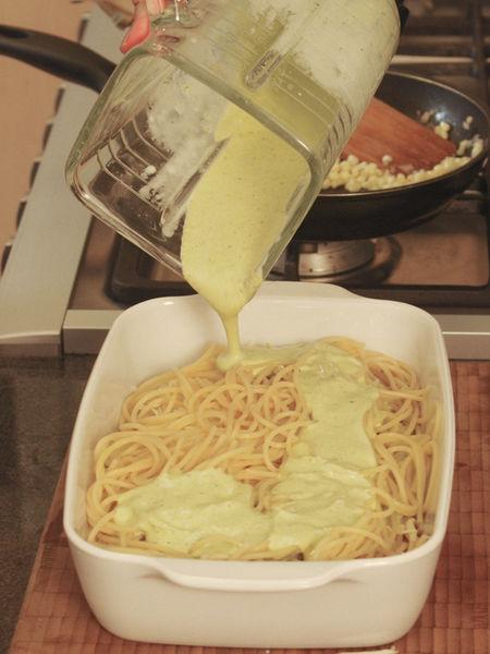 En un refractario colocar el espagueti, bañar con la salsa de chile, los elotes cocidos y añadir el queso chihuahua rallado. Se pueden hacer varias capas. Esto se puede tener listo con anticipación y meter a hornear justo antes de servir. Hornear a 300° F (150° C) durante 10 a 15 minutos o hasta que se derrita el queso.