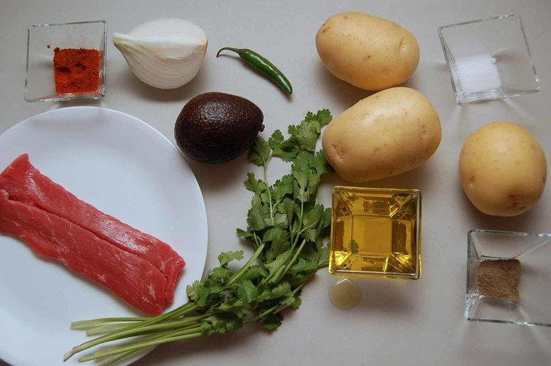 Ingredientes para receta 3 piezas de papa blanca 2 piezas de bistec de res 1 cucharada de paprika sal al gusto pimienta negra molida al gusto 1/4 taza de aceite de oliva Ingredientes para acompañar 1 pieza de aguacate 1/4 pieza de cebolla blanca 1 pieza de chile serrano 4 ramas de cilantro fresco sal al gusto