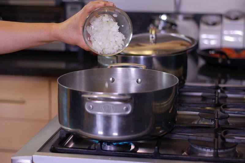 Calentar la olla con el aceite y agregar ajo y cebolla picada, moviendo constantemente durante tres minutos cuidando que no se doren.