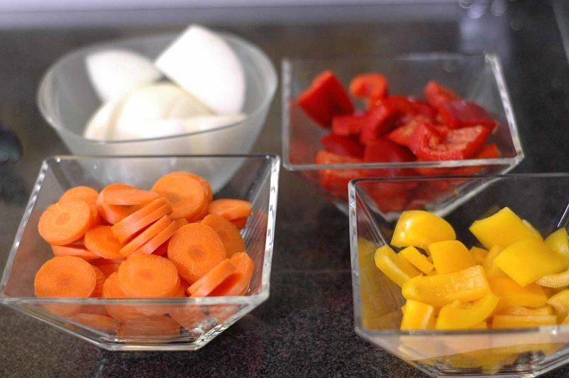 Cortar en trozos grandes la cebolla, pimiento morrón rojo y amarillo descartando la parte blanca, el brócoli en floretes, la zanahoria y diente de ajo en rodajas.
