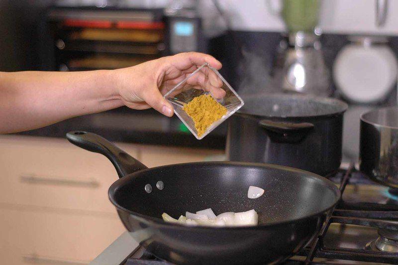 Añadir el ajo en rodajas y el curry. Revolver bien con la pala y continuar cociendo unos minutos más.