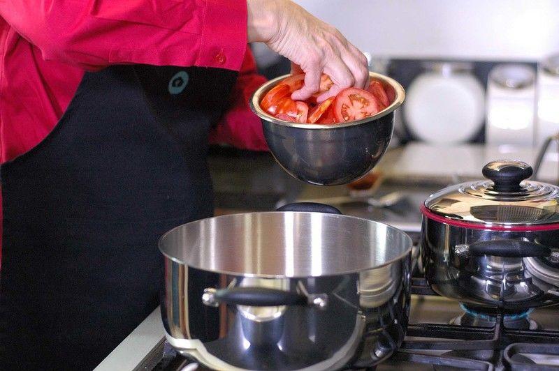 Calentar el aceite en la olla y colocar en la base una capa de rebanadas de jitomate.
