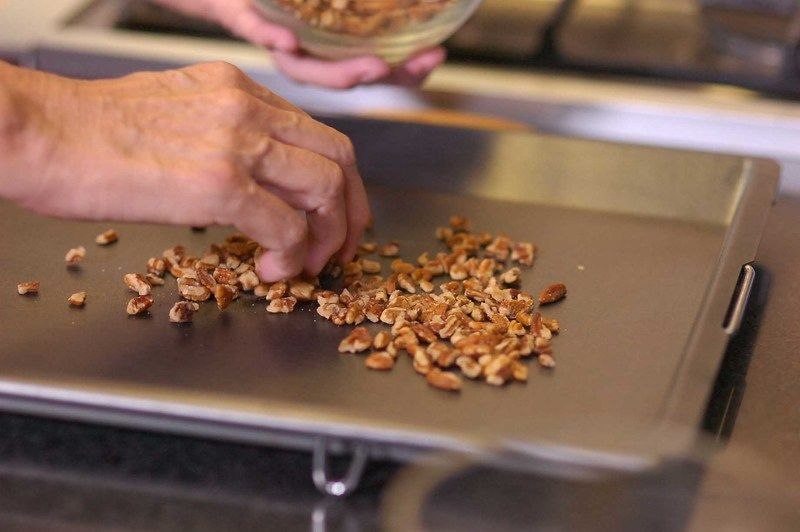 Poner la nueces esparcidas en una charola para galletas.