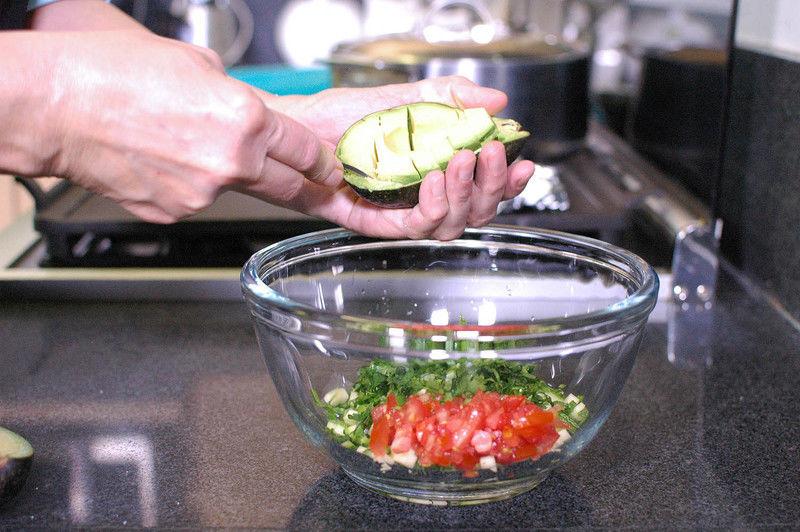 Añadir el aguacate en trocitos y sazonar con sal revolver bien con la ayuda de la pala.
