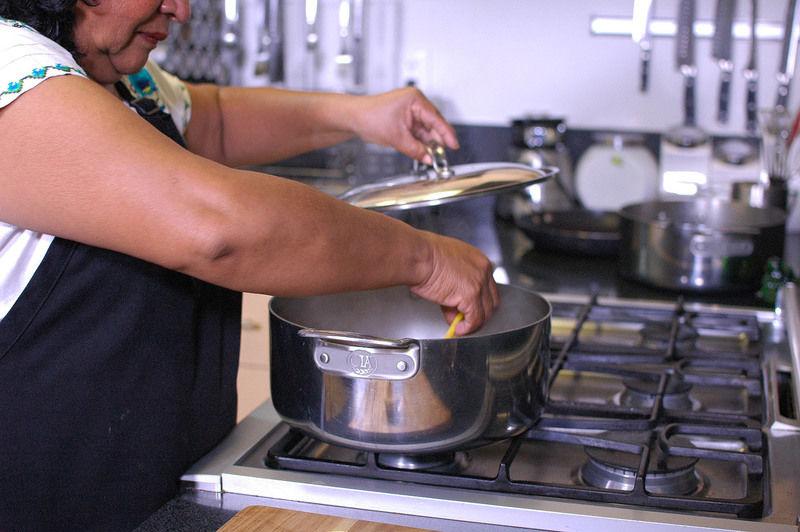 Retirar la carne ya cocida del caldo y deshebrar. Incorporar el caldo, las limas cortadas en rodajas, tapar la olla y retirar del fuego.