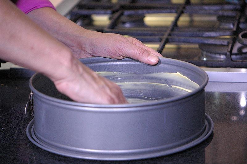 Engrasar un molde desmoldable para pastel con mantequilla.