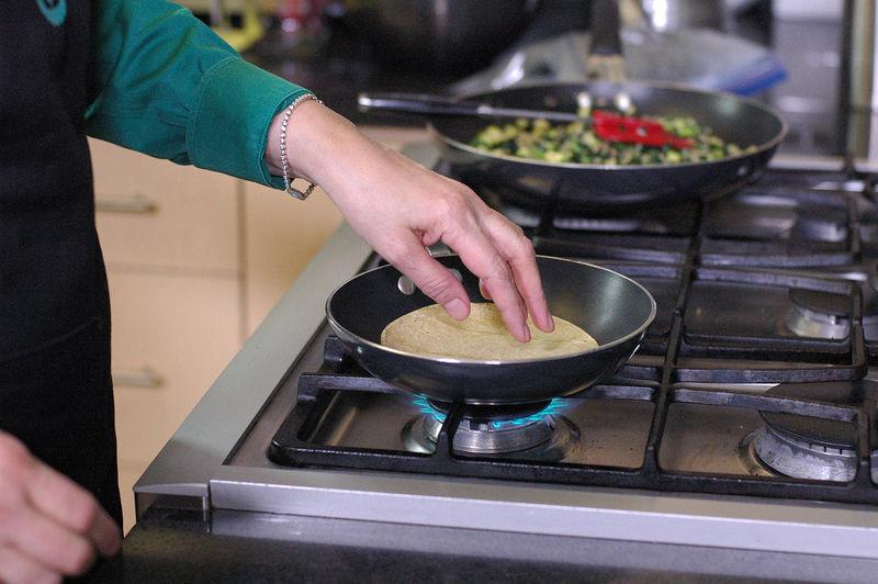 Para armar las enchiladas calentar las tortillas sobre un comal o sartén.