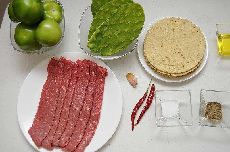 Ingredientes para receta 6 piezas de bistec de res 8 piezas de penca de nopal 6 piezas de tomate verde (tomatillo) 2 piezas de chile de árbol seco 1 diente de ajo sal al gusto 2 cucharadas de aceite de oliva pimienta negra molida al gusto tortilla de maíz al gusto