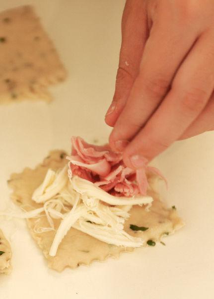 Colocar una cucharada de jamón picado y una de queso desmenuzado en el centro de un cuadro de masa. Poner otro cuadro de masa sobre el relleno y sellar las orillas presionando fuerte con los dedos.
