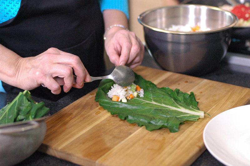 Colocar una hoja de acelga sobre la tabla para picar y rellenar con un poco de la mezcla de arroz.