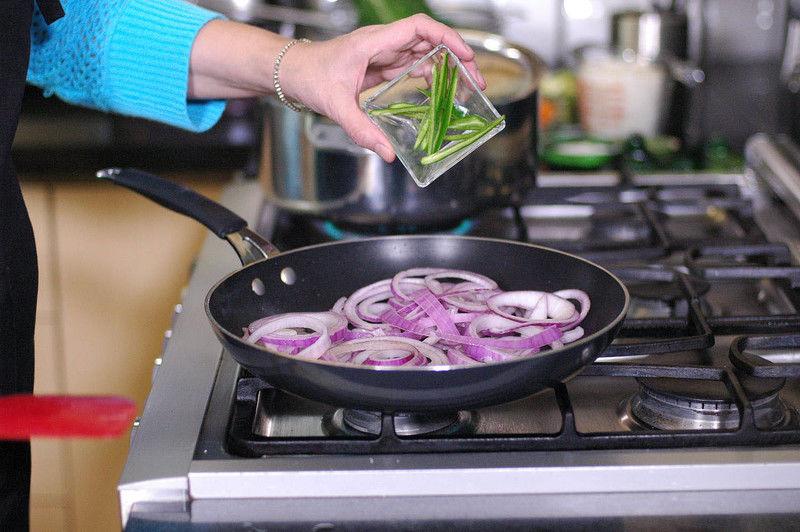 Calentar las dos cucharadas de aceite en un sartén y sofreír la cebolla en rodajas, tiras de chile serrano.
