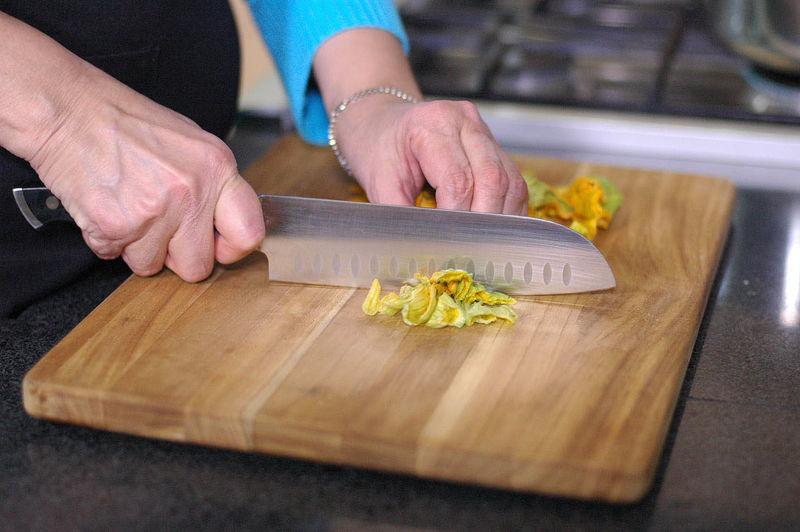 Picar finamente la cebolla y las flores de calabaza, y la calabacita en cuadros a tamaño bocado. Reservar.