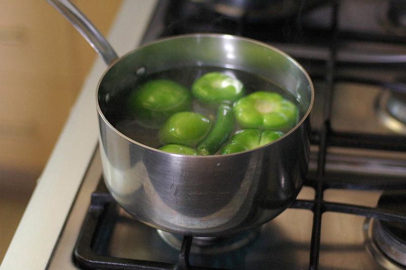 Para preparar la salsa poner a hervir los tomates verdes, chile serrano y diente de ajo en una olla honda con un poco agua durante 5 minutos, cuidando que no se rompan los tomates.