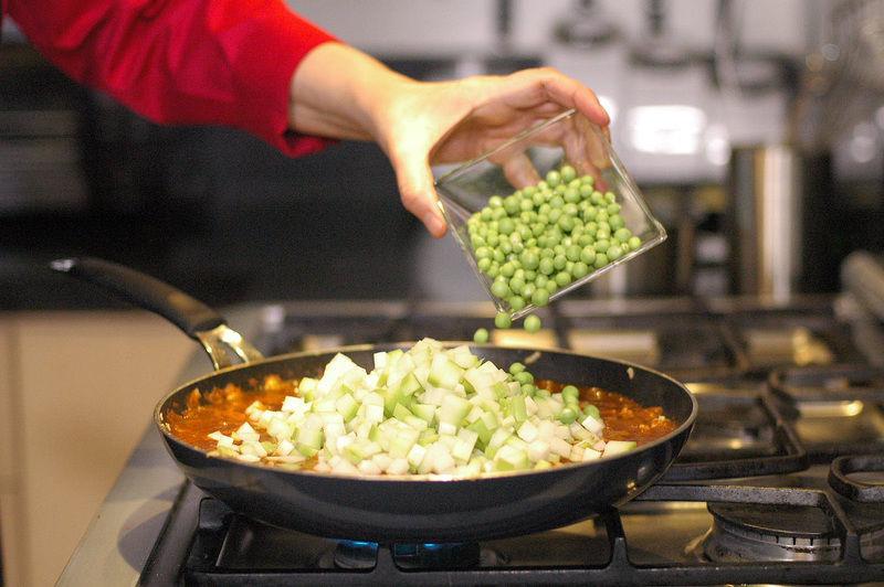 Añadir chícharos y rectificar sazón. Tapar y dejar cocer a fuego bajo durante 15 minutos o hasta que estén cocidas las verduras.