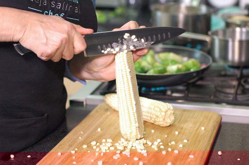 Desgranar los elotes con un cuchillo sobre la tabla para picar. Es mejor rebanar sólo dos filas a la vez y después repasar con el cuchillo para sacar toda la pulpa.