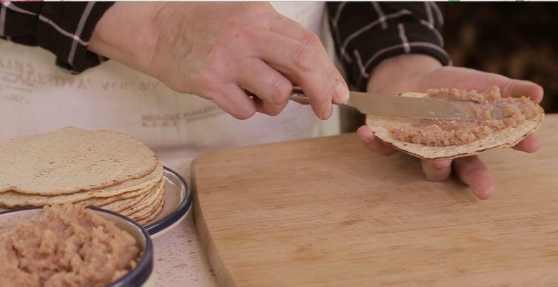 Para armar las tostadas; untar un poco de frijoles refritos sobre la tostada.