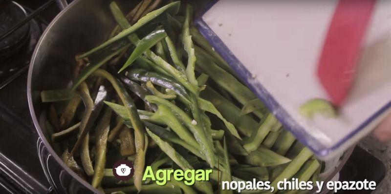 Añadir tiras de chile poblano, chile serrano, y las hojas de epazote picadas, revolver bien con la pala.