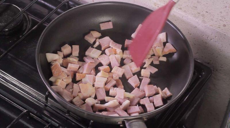 Para preparar el aderezo; calentar el sartén y cuando esté caliente, sofreír el tocino picado moviendo constantemente hasta que se vea dorado, pero no quemado.