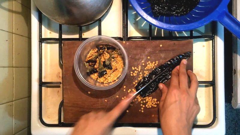 Desvenar los chiles pasilla, es decir, retirarles la cola y quitarles las semillas que vienen dentro.