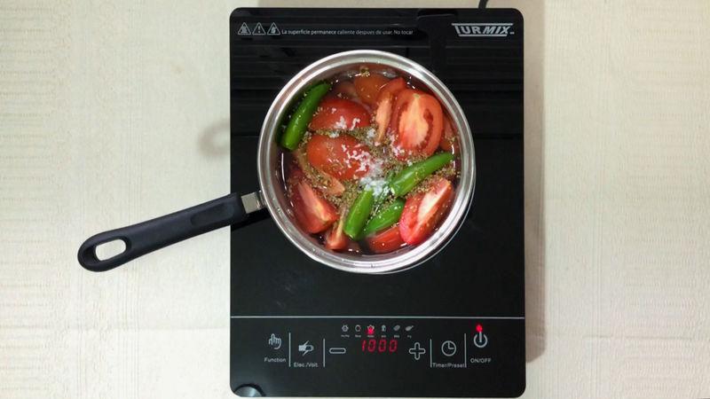 Agrega a la olla los 250 ml. de agua junto con los jitomates, el chile serrano así como la sal y el orégano, debe de usarse muy poca agua para que la salsa quede espesa y con buen sabor.