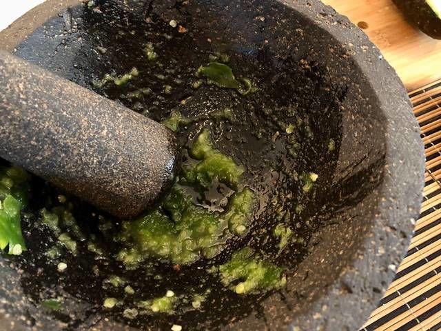 Remoja el molcajete con poca agua, coloca la sal y el chile serrano, comienza a mezclar los ingredientes.