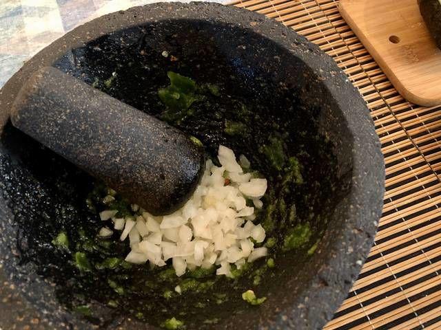 Añade el cilantro y la cebolla, trata de molcajetear lo más que se pueda la cebolla.