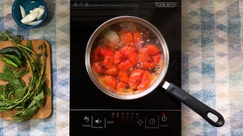Añade 1/4 de cebolla blanca y 1 diente de ajo, ponlos a fuego alto por 10 minutos o hasta que los jitomates se les desprenda la piel.