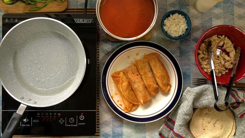 Una vez frita la tortilla cúbrela completamente en la salsa, puedes utilizar unas pinzas o con tus manos para que no se rompa, al final colócala en el plato, añade pollo y enrolla.