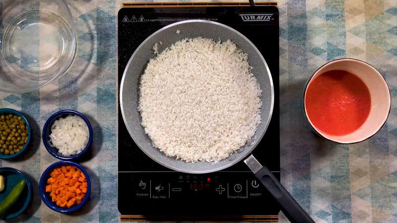 En un sartén coloca el aceite y deja calentando a fuego alto, agrega el arroz y fríe durante 3 a 5 minutos hasta que tenga un tono tostado y uniforme. Pasado este tiempo coloca media cebolla picada finamente.