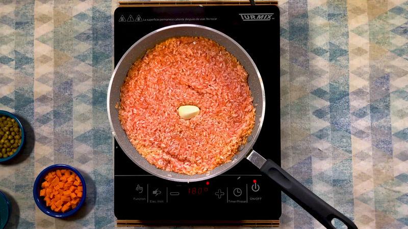 Agrega la salsa roja y mezcla muy bien, deja de 3 a 5 minutos a que el arroz absorba el jitomate hasta que se haga una pasta espesa, añade el diente de ajo.