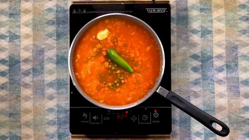 Mezcla bien el arroz con jitomate y el caldo, agrega las verduras, la zanahoria, chícharos y el chile serrano. Cuando comience a burbujear, tapa a fuego bajo durante 15 minutos.