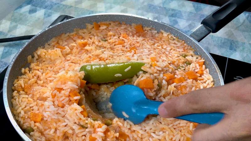 Ya casi está listo el arroz, puedes con una cucharada levantarlo y verás seco el fondo, vuelve a taparlo durante 3 minutos a fuego muy bajo para terminar la cocción.
